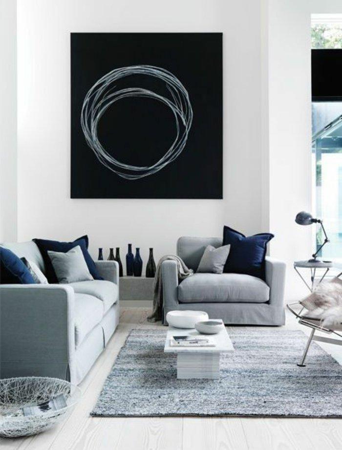 schwarzes Bild mit runden Kreisen, Sofa und Sessel in grauer Farbe - Wohnzimmer in grau