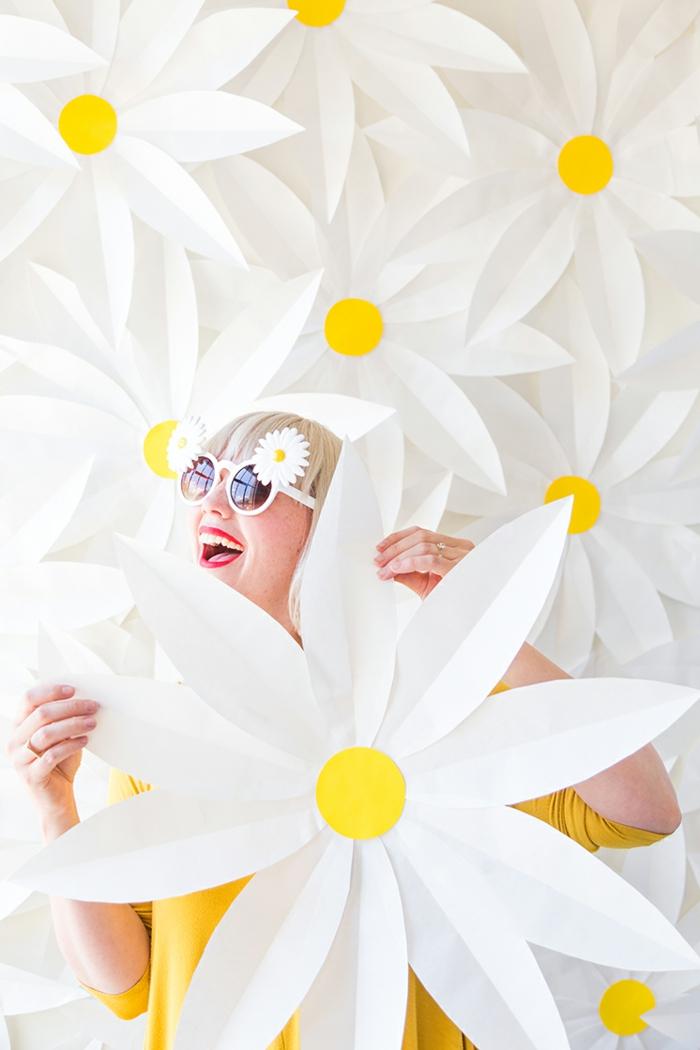wanddeko aus papier, papierblumen, gänseblumen, diy, frau mit blonen haaren und sonnnenbrillen