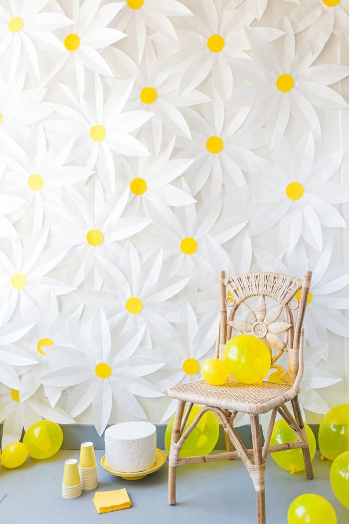 wanddeko aus papier, große gänseblumen, geflochtener stuhl, ballons