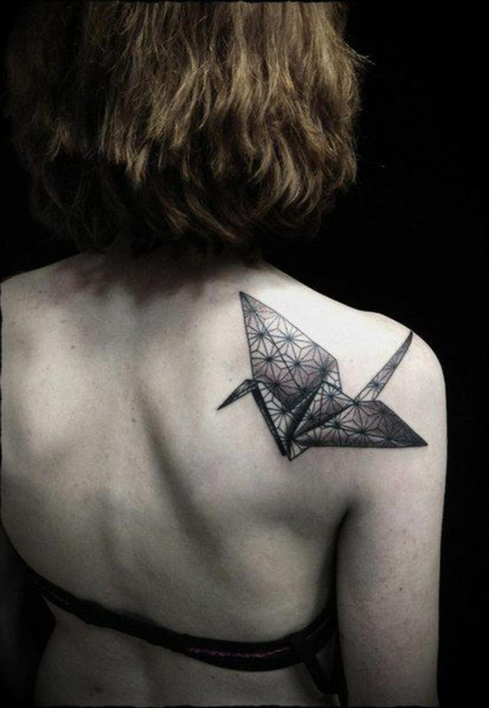 werfen sie einen blick auf diese idee für einen origami tattoo - ein kleiner schwarzer origami vogel auf dem schulterblatt einer jungen frau