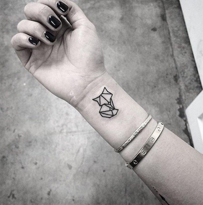 hand mit nagellack, einer schwarzer katzen tattoo auf handgelenk und armband