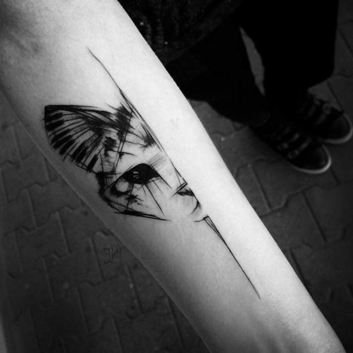 hand mit einem tatoo katze - eine schwarze katze mit schwarzen augen