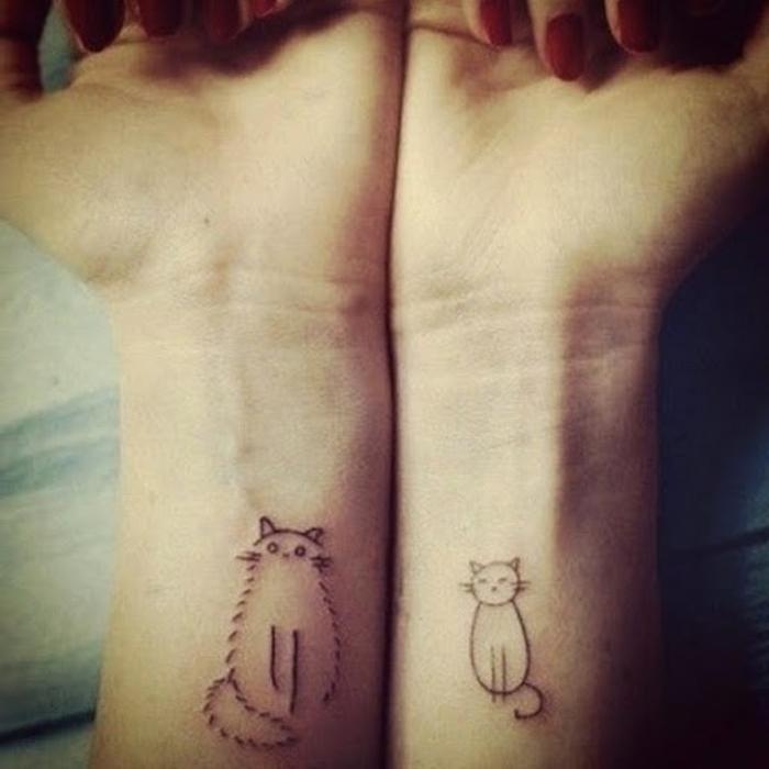hier sind zwei hände und zwei kleine schwarze katzen tätowierungen auf handgelenk