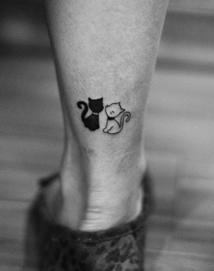 noch eine umserer ideen zum thema katzen tattoo auf bein - eine schwarze katze und eine kleine weiße katze mit schwarzen vibrissen