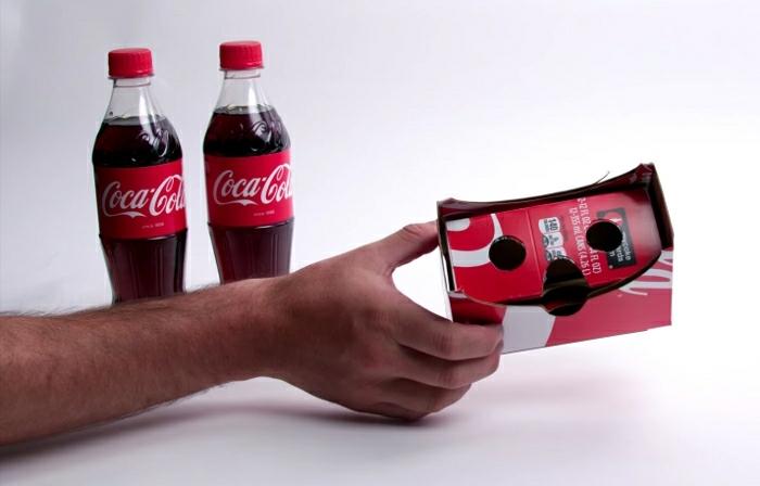 hier ist eine hand mit einer roten vr brille aus coca-cola flaschen - zwei rote coca-cola flaschen