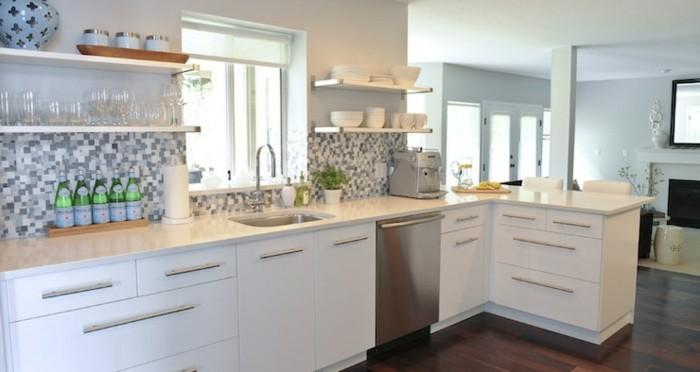 L-Küche mit Laminatboden, Mosaik-Küchenrückwand in grauen Nuancen, Fenster vor dem Waschbecken