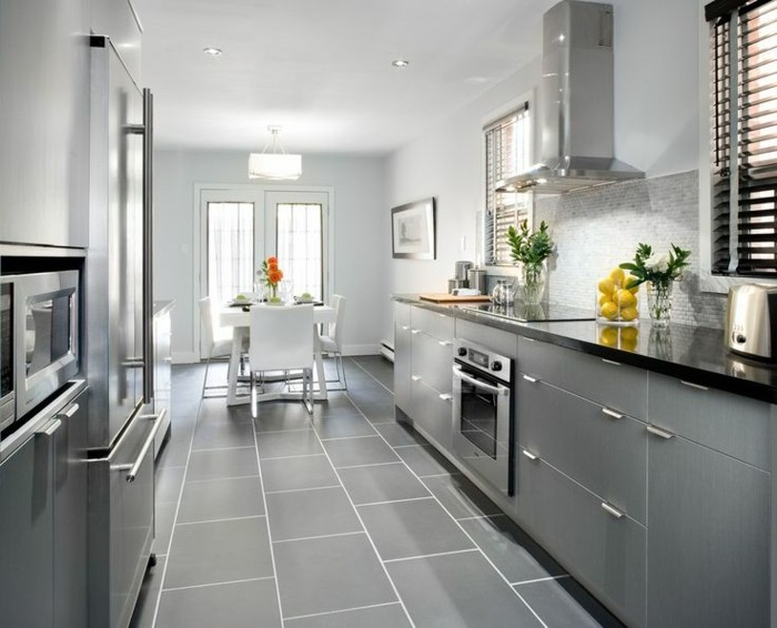 graue Küche mit grauen Fliesen am Boden, Kühschrank mit zwei Türen, Übergang zum Esszimmer