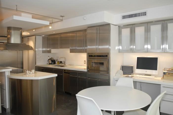 Küchen in Weiß mit Metllmöbeln, runder weißer Esstisch mit drei weißen Stühlen, Schreibtisch mit Computer