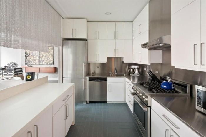 Küche mit kleinen schwarzen Bodenfliesen, weiße Küchenschränke mit Standardgriffen aus Metall