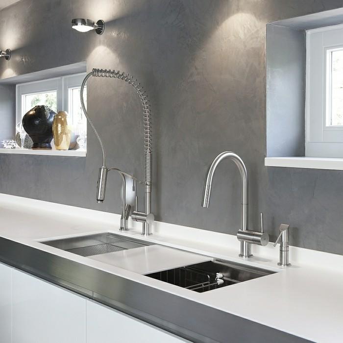 Küche mit grauen Wänden, weißer Tischplatte, Waschbecken mit Obst- und Gemüsenkorb