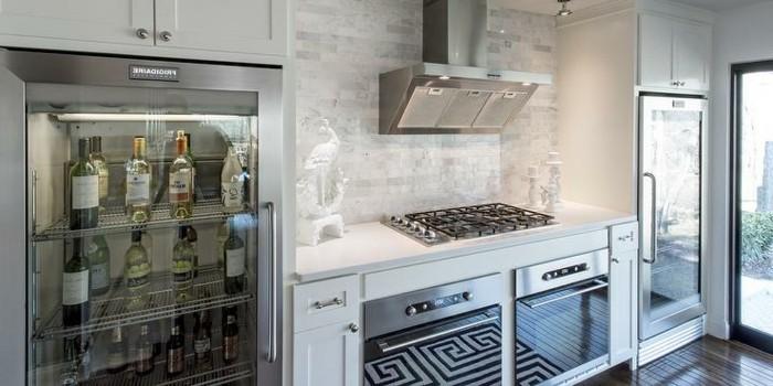 Küche in hellen kalten Farben mit Getränkekühlschrank voll mit Alkoholflaschen, Gas-Platten