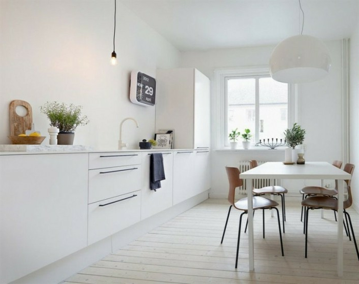 Holzboden in der Küche, elektronische Wanduhr in quadratischer Form, Kräuter, helle Küche