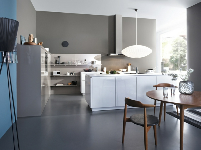 weiße Küchenfronten, grauer Boden, graue Wände, Stehlampe, runder Holztisch, Kronleuchter aus Papier