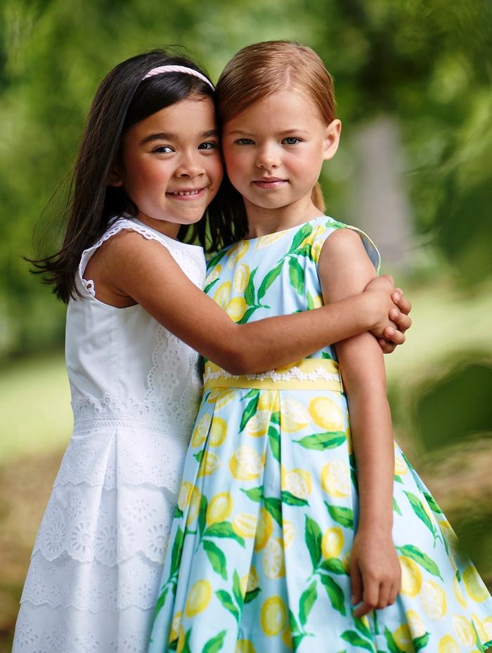 festliche Kindermode, weißes Kleid mit Spitze, weites Kleid mit Zitronen-Motiven, Sommertrends