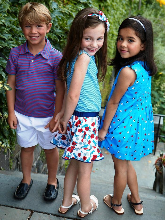 festliche Kindermode, Jungenkleidung- gestreifte Bluse, kurze weiße Hose, Mädchenkleidung- blaues Kleid mit Blumenmotiven, weiter Rock mit Top