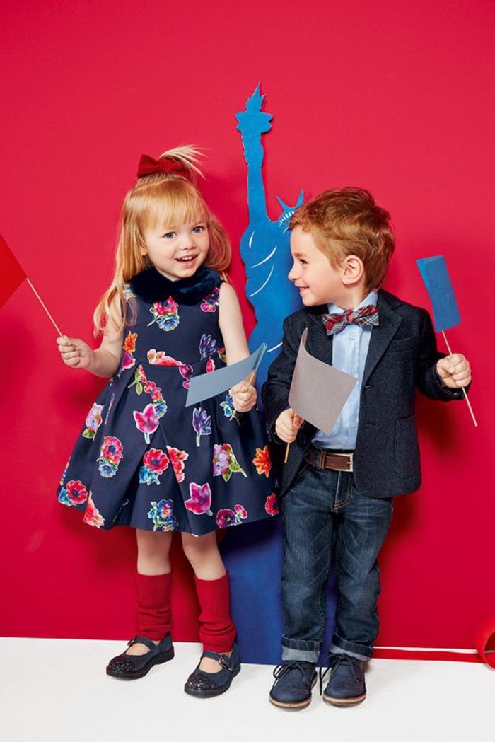 festliche Kindermode, Mädchenkleidung- weites dunkelblaues Kleid mit Blumenmotiven, Jungenkleidung- Jeans in Kombination mit Hemd, Blazer und Fliege