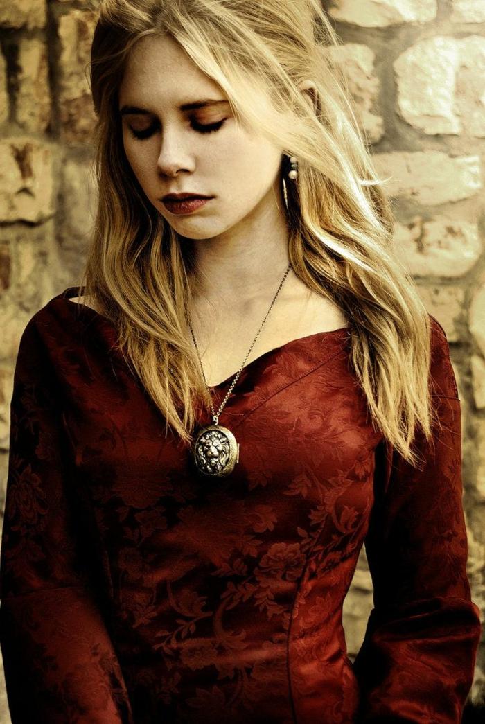 rotes Kleid, blonde Haare. ein Medaillen mit einem Löwen geflochtene Frisur