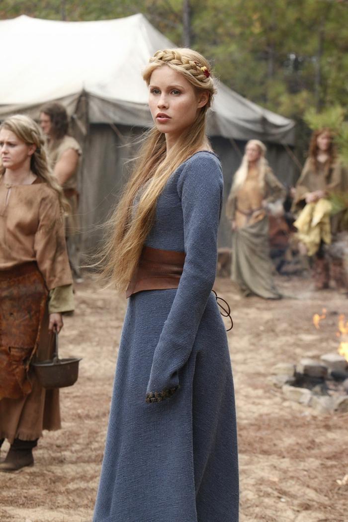 blondes Mädchen mit geflochten Frisur in einem mittelalterlichen Filmset mit blauem Kleid