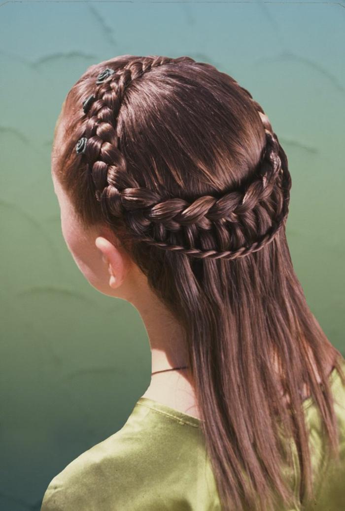 eine zarte Mädchen Frisur von Mittelalter von braunen Haar mit grünen Blumen als Haarschmuck