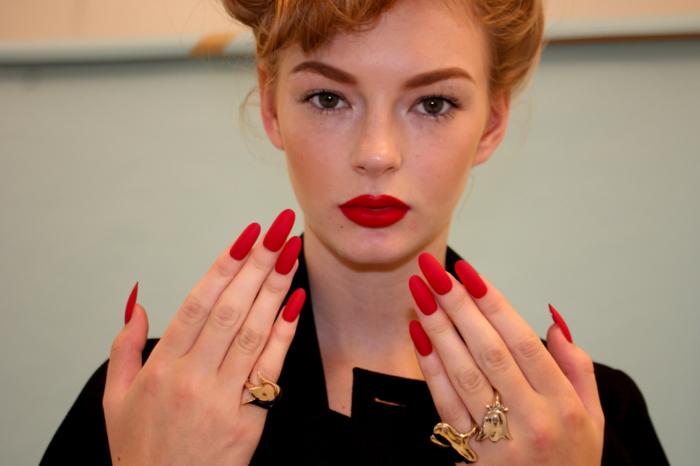 gelnägel spitz frau model mit roten lippen und rote lange gelnägel goldene ringe deko retro stil schminke frisur