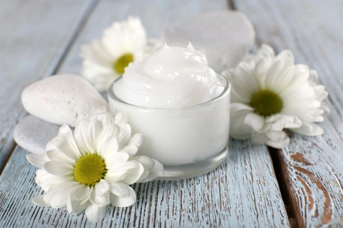 Hautcreme aus Sheabutter und Kokosöl, ätherischen Ölen, Glasbehälter für Kosmetik, weiße Steine