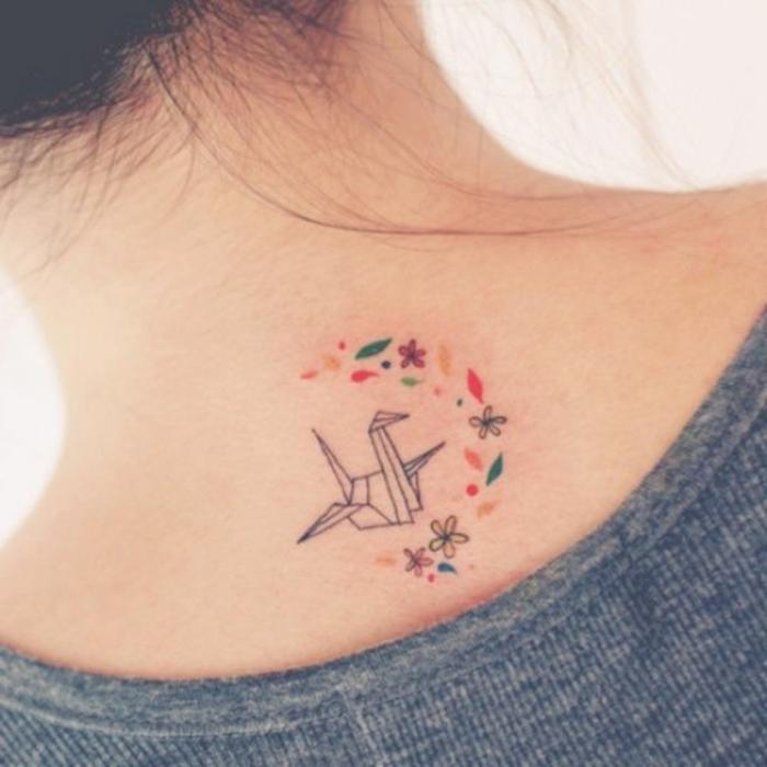 tolle idee für einen kleinen origami tattoo auf dem nacken einer jungen frau - hier ist ein fliegender origami vogel und viele kleine blumen