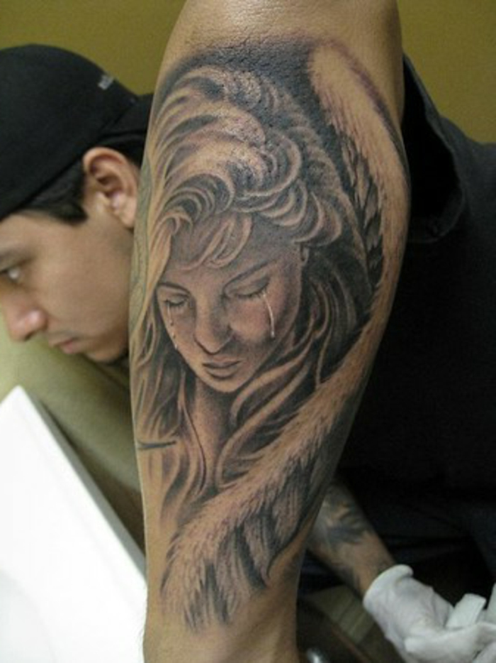 eine traurige und weinende frau mit großen engelsflügeln mit weißen federn - idee für einen tattoo engel für die männer