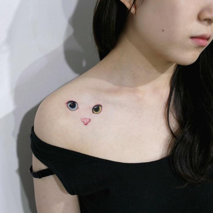 idee für einen schönen katzen tattoo auf schulter für eine junge frau - hier ist eine katze mit großen grünen augen und einer pinken nase