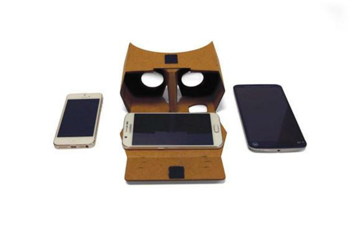 vr vrille aus pappe, zwei kleine okulare, zwei weiße handys und ein großes schwarzes smartphone
