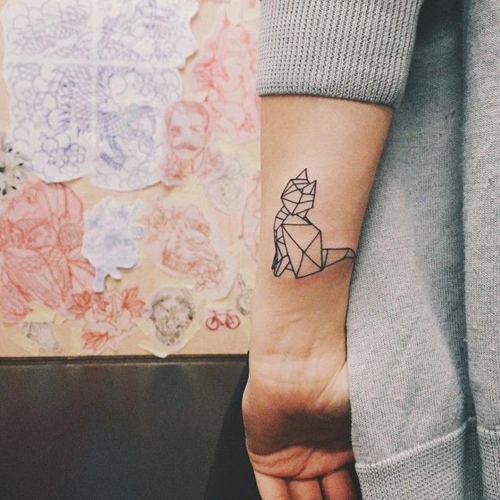 eine hand mit einer kleinen schwarzen katzen tätowierung - idee für einen tattoo für die frauen