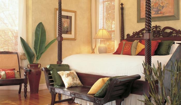 orientalisch einrichten großes bett mit vielen kissen und exotischem design palmen blumen natürlich