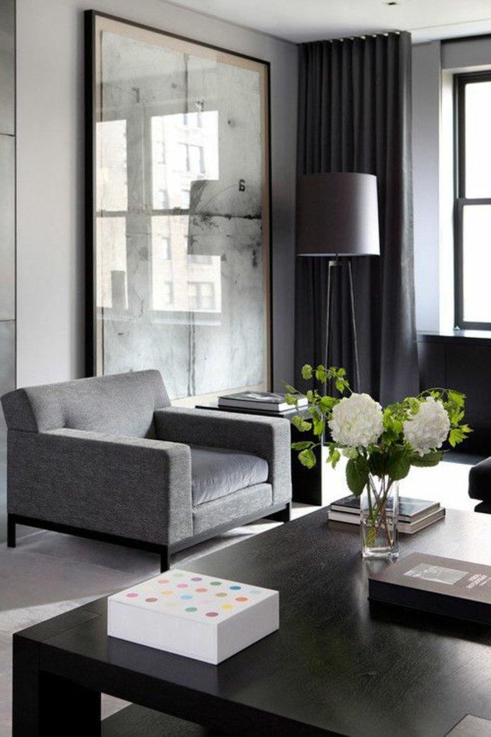 großes Wandbild in weißer Farbe das das Licht von Fenster verspiegelt Wohnzimmer grau