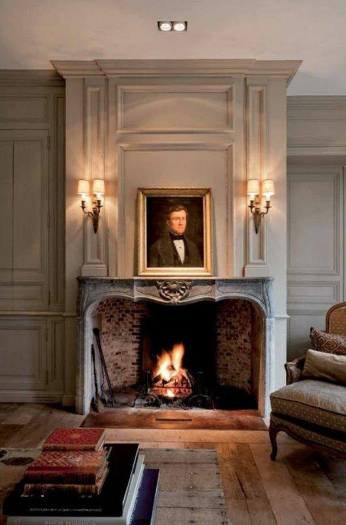 graues Zimmer mit einem Kamin, symmetrisch gestellte Lampen und Bücher