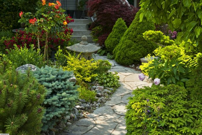 eine japanische Garten Skulptur ein Pfad und viele Pflanzen - Vorgarten pflegeleicht gestalten