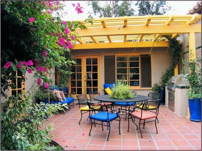 ein Garten mit bunten Möbel und rosa Kletterpflanzen, rote Fliesen - Gartenbeete gestalten