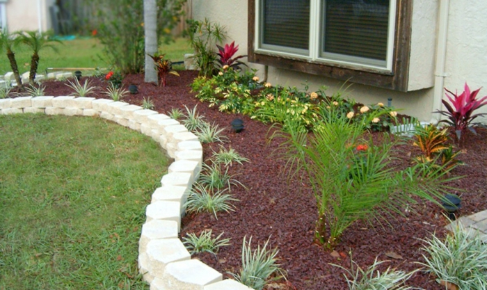 Vorgarten pflegeleicht gestalten - mit weißen Steine die kleinen Pflanzen von dem Rasen teilen