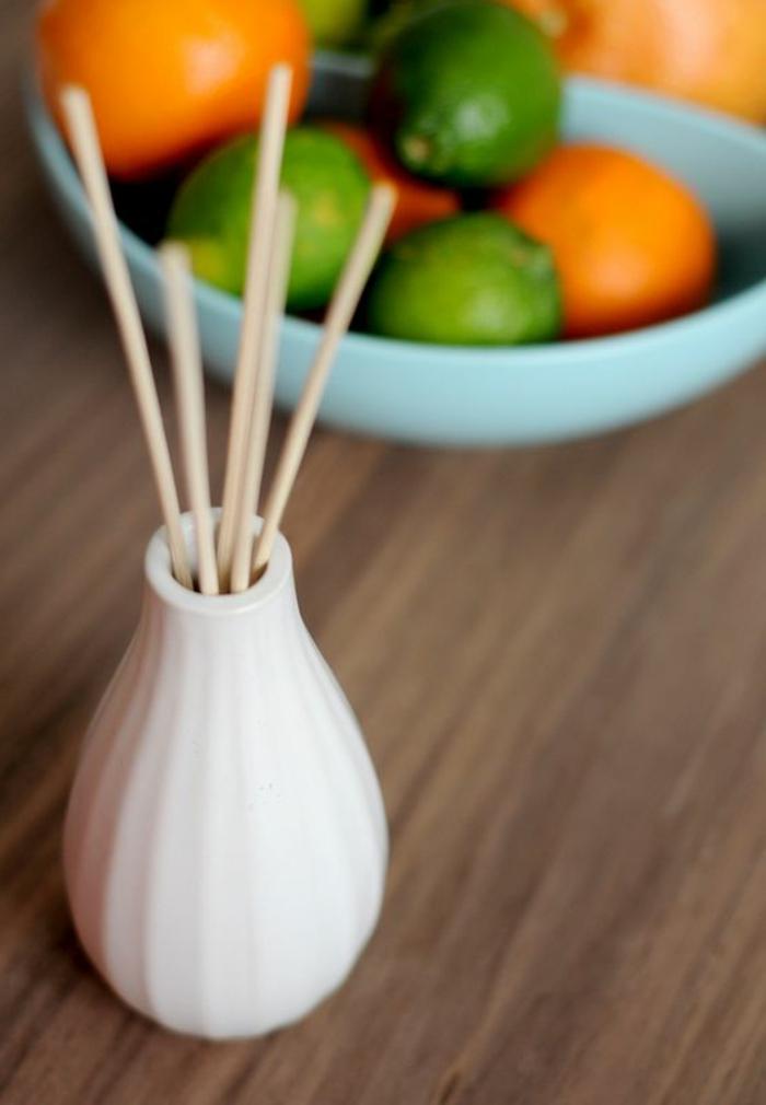 blaue schale, obst, limetten, orangen, tisch, weiße vase, raumduft
