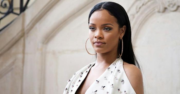schwarze glatte Frisur - Rihanna Haare, große Ohrringe aus Gold, weißes Kleid mit Muster
