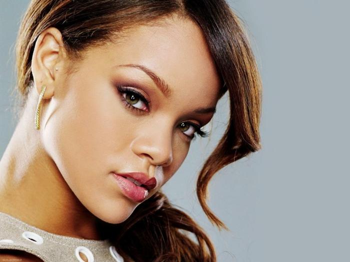 ein niedliches Foto von Rihanna - eine Lock als Pony rosa Lippenstift und hängende Ohrringe