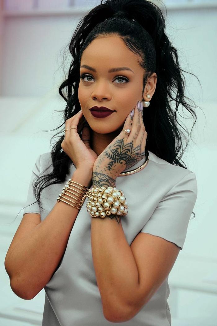 niedlicher Look von Rihanna mit zwei Armbänder mit Perlen, sprödes schwarzes Haar mit Hochsteck Frisur - beste Frisuren