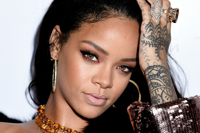 schwarzes Haar, goldene Ohrringe und ein Halsband mit Steinen, glatte Frisur - Rihanna Frisur