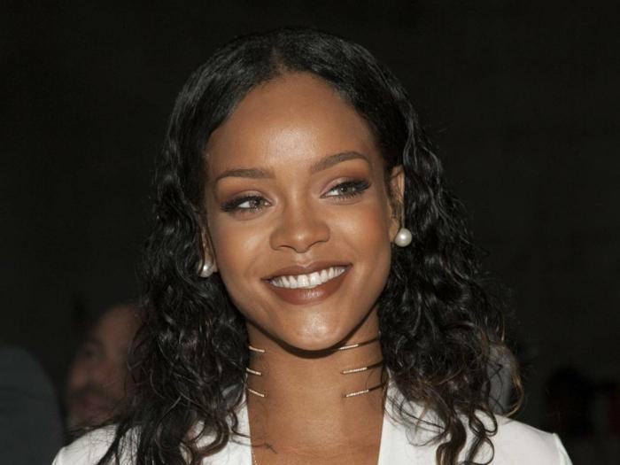 Schwarzes lockiges Haar Perlen Ohrringe, brauner Lippenstift - Bilder von Rihanna
