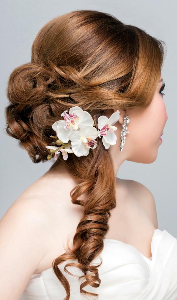 Brautfrisuren für lange Haare mit großen Locken, frei fallendem Pony und einer weißen Orchidee als Haarschmuck