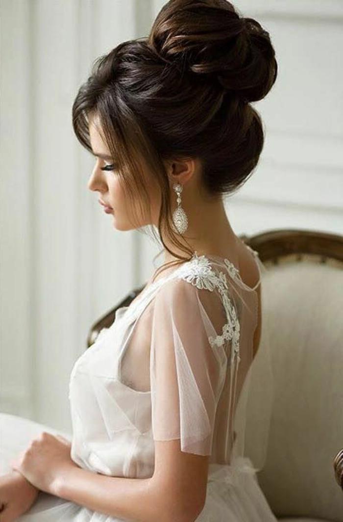 elegante Braut am Hochzeitstag mit weißem Tüllkleid, Dutt mit viel Volumen, frei fallendes Pony