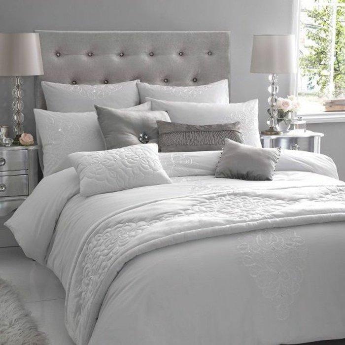 Schlafzimmer grau - graue Wände, zwei symmetrisch gestellte Lampen, viele Kissen