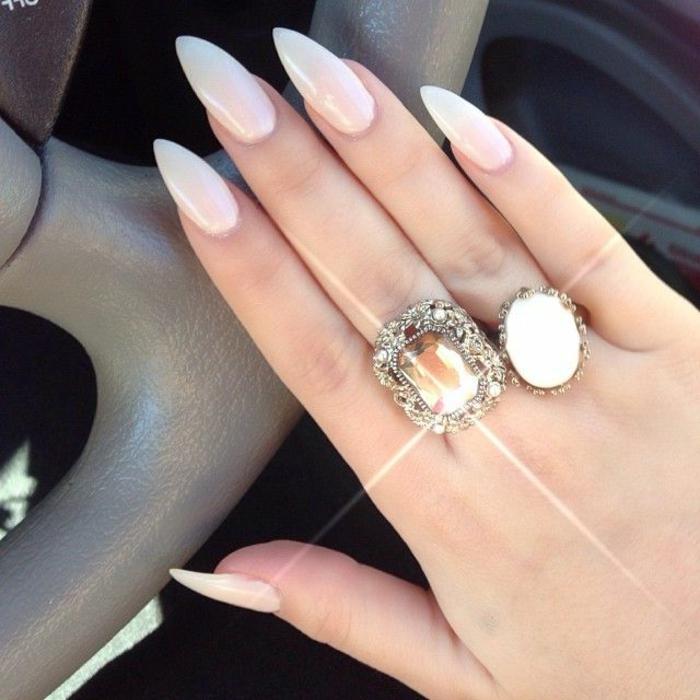 nägel mandelform schöne hand mit zwei großen ringen weiße mandelförmige nägel selfie im auto