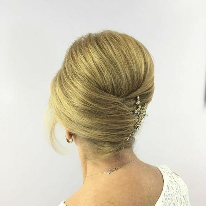 Frauenfrisuren für ältere Damen, strenge Steckfrisur mit frei fallender Strähne, Haarschmuck mit Blumen