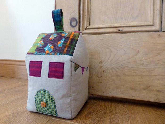 Türstopper Sack in der Form eines Hauses mit Fenster und Tür mit Knopf als Griff