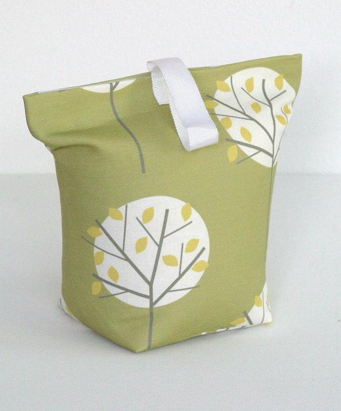 grüne Tasche mit Bäumen voller schwere Sachen dient als Türstopper Sack