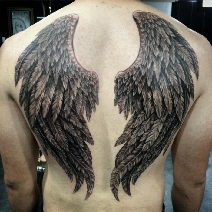 ein man und sein engel tattoo mit zwei schwarzen engelsflügeln mit langen schwarzen federn